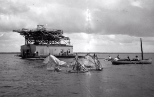 A towline drags the wrecked Langley Aerodrome machine after an unsuccessful test.  The houseboat launchpad with its catapult on the roof can be seen.  Source:  Smithsonian