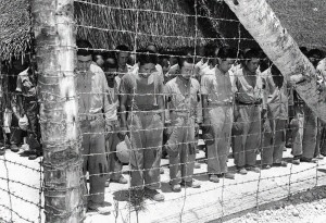 Japanese Prisoners of War on Guam react to the announcement of Japan's surrender and stand, with heads bowed, as they listen to the address of the Japanese Emperor over the camp's loudspeakers.  Photo Credit:  US Navy