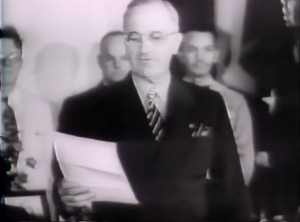 President Truman reads his prepared statement accepting the Japanese surrender message and setting in motion the end of the war.  Photo Credit:  Frame Capture from News Reel Footage from August 1945