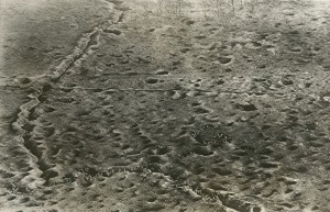 """Birdseye view of a battlefield on the Somme front. Photograph shows a battlefield on the Somme front in France during World War I, with French troops moving through trenches and shell craters into an area formerly held by the German army. Caption on verso states """"This remarkable photograph was made by a French aviator from a height of 590 feet."""""""