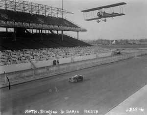 "Katherine Stinson, in her Partridge-Keller ""Looper"" Biplane, races Dario Resta, winner of the 1916 Indianapolis 500, driving in his Peugeot L45 racer, on the oval track -- here photographed in a practice run before tickets were sold and the crowds packed the stands."
