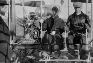 Katherine Wright sits beside Wilbur in the Wright plane at Pau, France, while Wilbur, at far left, looks on.