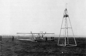The Wright plane is prepared for launching on its rail, with the launch catapult tower in plain view -- the weight is already hauled up to the top in preparation for launch.
