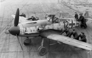"Luftwaffe ground-crew (""black men"") positioning a Bf 109 G-6 ""Kanonenvogel"" equipped with the Rüstsatz VI underwing gondola cannon kit. Note the slats on the leading edge of the port wing. JG 2, France, late 1943, around the time of the ill-fated Münster raid."