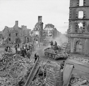 An American-made Sherman tank drives through the ruins of Fler on August 17, 1944, soon after its liberation.  The town was devastated twice, in both world wars.  Photo Credit:  The Imperial War Museums, Photograph B 9330