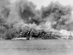 The burning scene after the Japanese attack on Pearl Harbor.  USS Oklahoma (BB-37) can be seen capsized in the foreground, while behind is USS Maryland (BB-46) and USS West Virginia (BB-48), which is burning to the right side.  Photo Source:  National Archives Identifier 295984