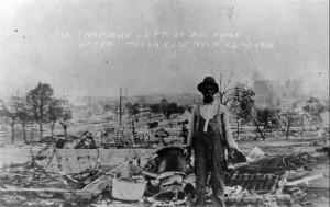 An African-American man stands before the ruins of his home in Tulsa after the firebombing.