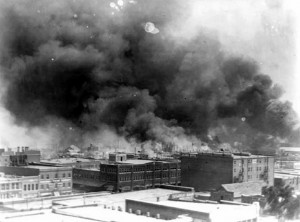 The Black Wall Street district of Tulsa burns as thick black smoke fills the skies.