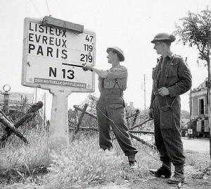 British soldiers in Normandy point to a road sign, c. June 1944.